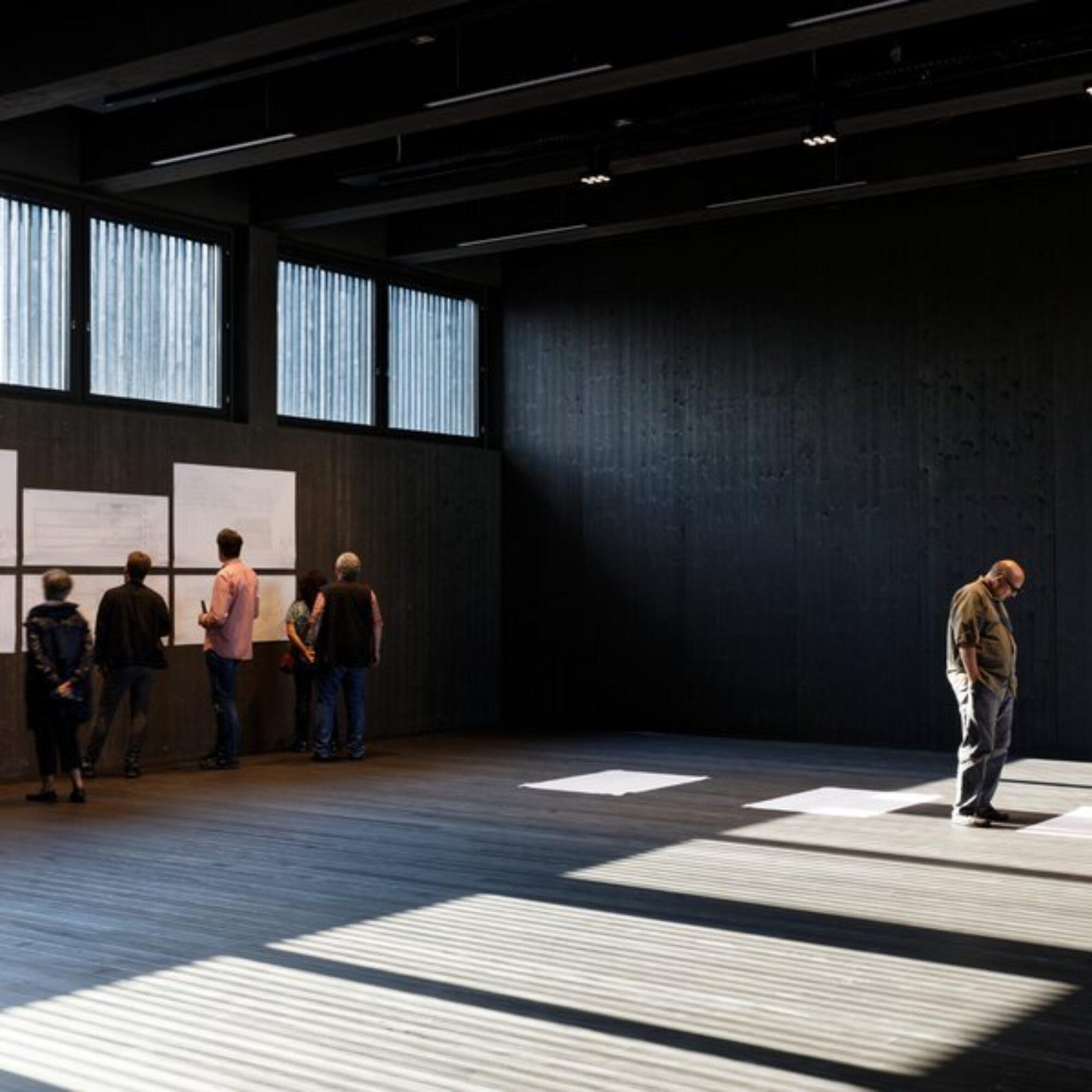 Grosser, sonnenerleuchteter Raum mit fünf Menschen, die grosse Plakate an der Wand oder am Boden studieren.