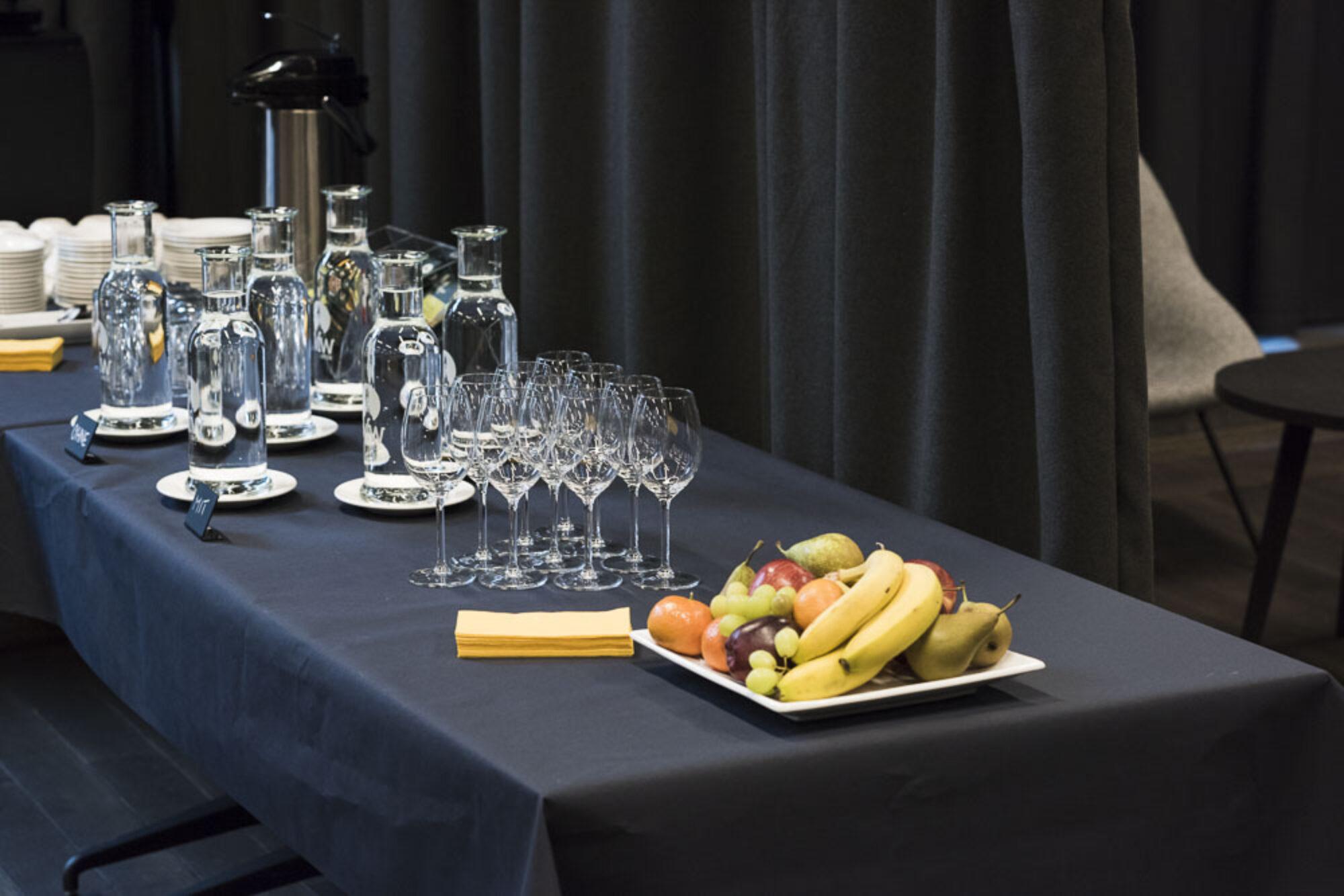 Tisch mit Früchten, Gläsern und Wasserkaraffen auf blauem Tisch.
