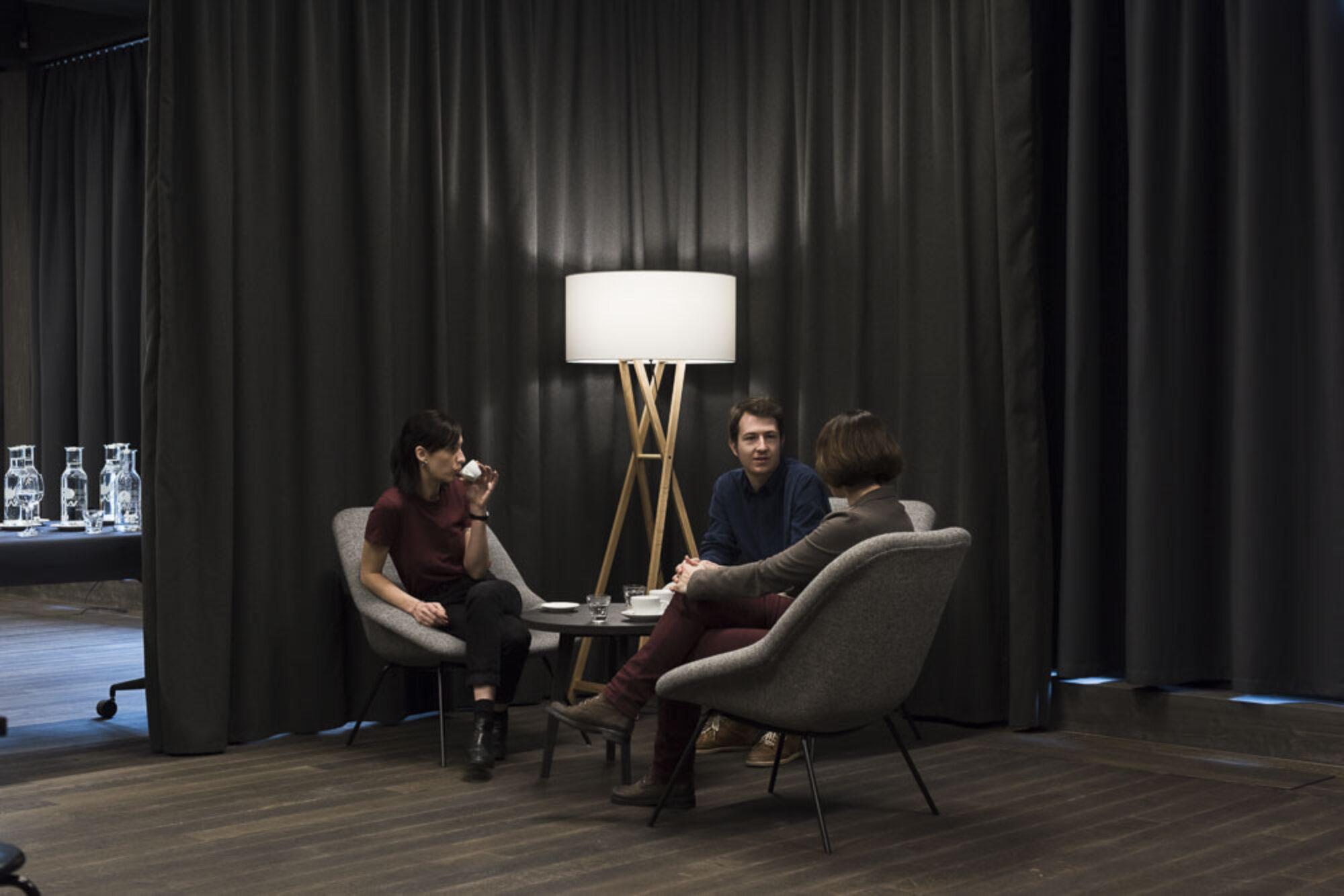 Drei Menschen im Gespräch vertieft, auf Stühlen sitzend, Wasser-Karaffen im linken Hintergrund auf mobilem Tisch.