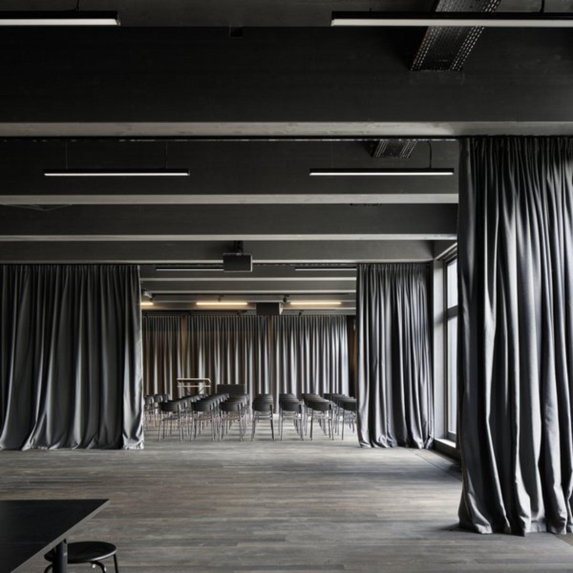 Grosser Raum, mit Blick zu aufgereihten Stühlen und gerafften Vorhängen auf beiden Seiten und hinten an der Wand.