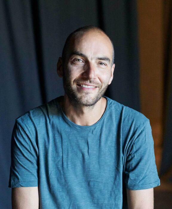Portrait eines Mannes, der direkt zur betrachtenden Person blickt und lächelt.