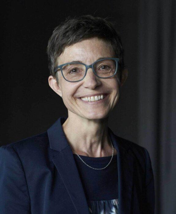 Portrait einer Frau, die direkt zur betrachtenden Person blickt und lacht.