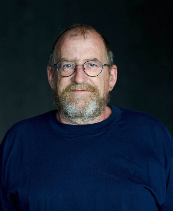 Portrait eines Mannes, der direkt zur betrachtenden Person in die Kamera blickt.