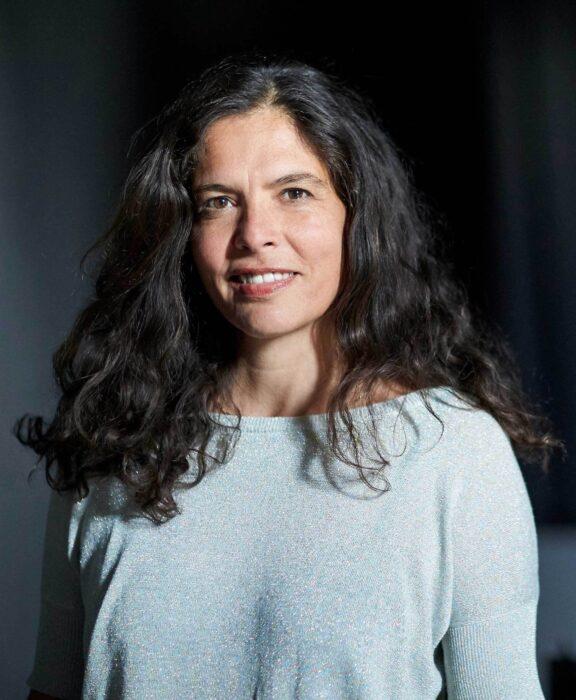 Portrait einer Frau, die direkt zur betrachtenden Person blickt und lächelt.