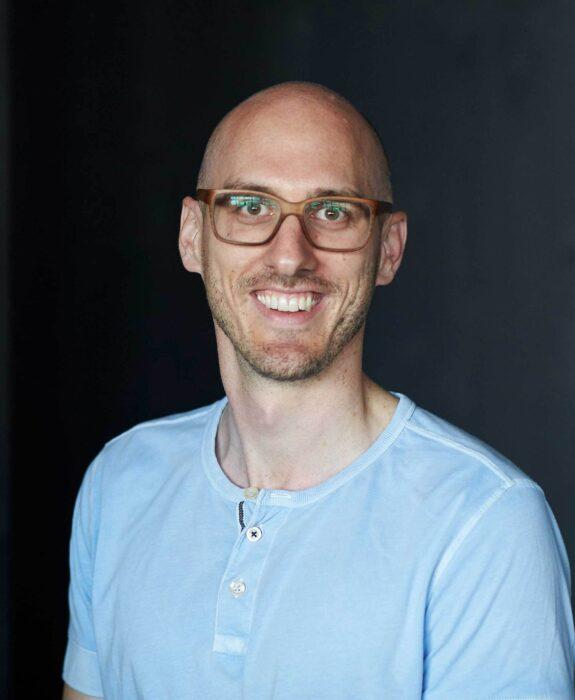 Portrait eines Mannes, der zur betrachtenden Person blickt und lacht.